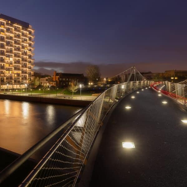 de fietsersbrug over de leie naar de K-tower tijdens de zonsondergang, Kortrijk, Belgie